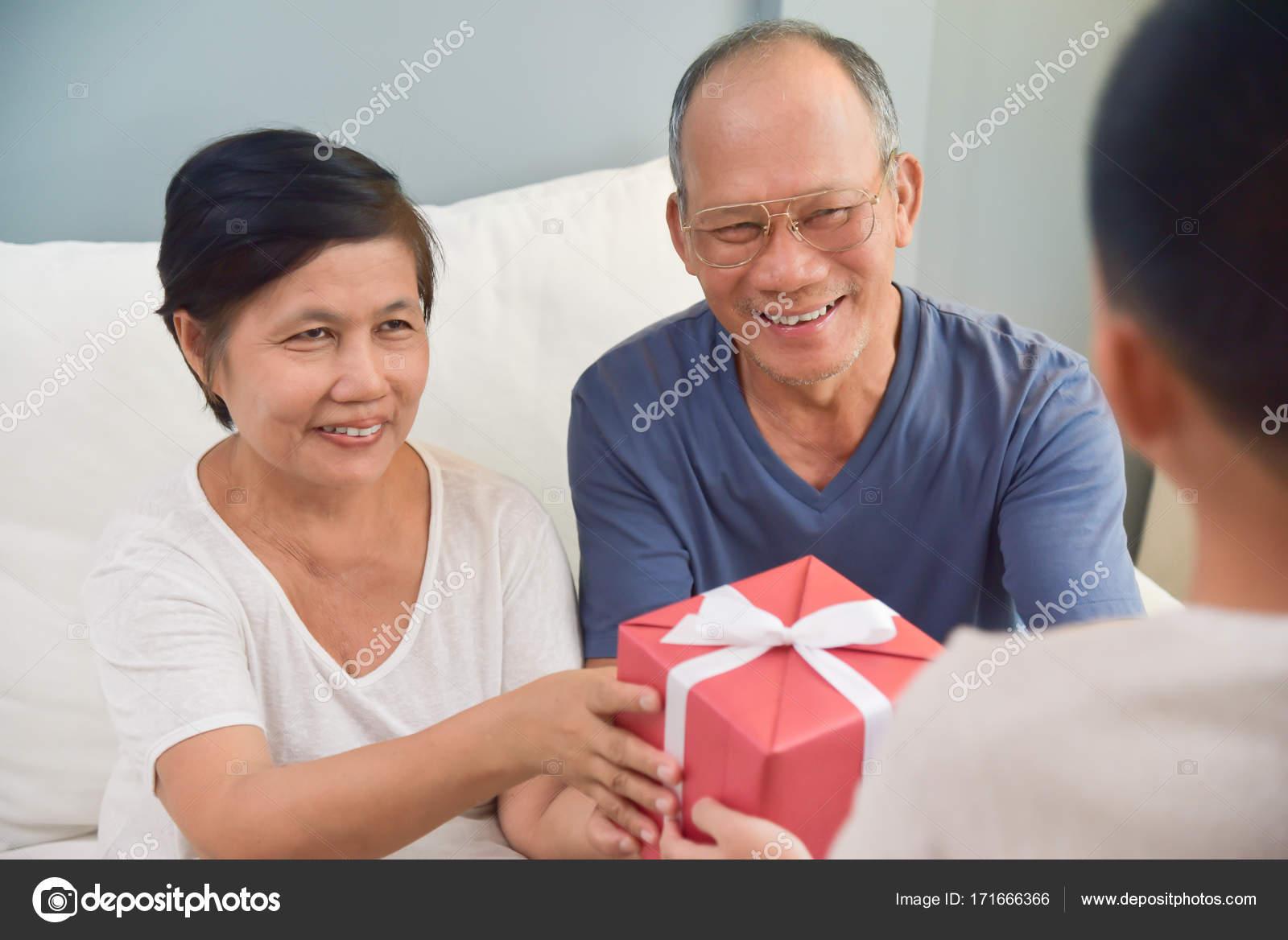 boîte-cadeau grand-père et grand-mère recevant rouge — photographie