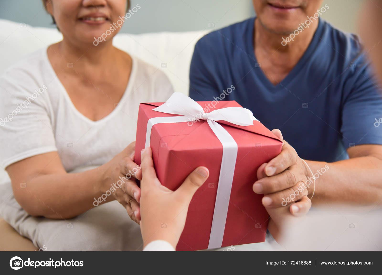 garçon asiatique donnant une boîte cadeau rouge à grand-père et