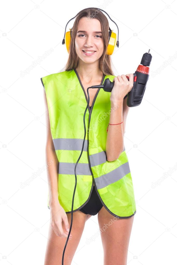 attractive young brunette woman in builder vest, earmuffs and black bikini hold screwdriver