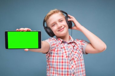 Boy with headphones holding mobile
