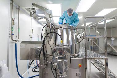 scientist looks in steel tank in laboratory