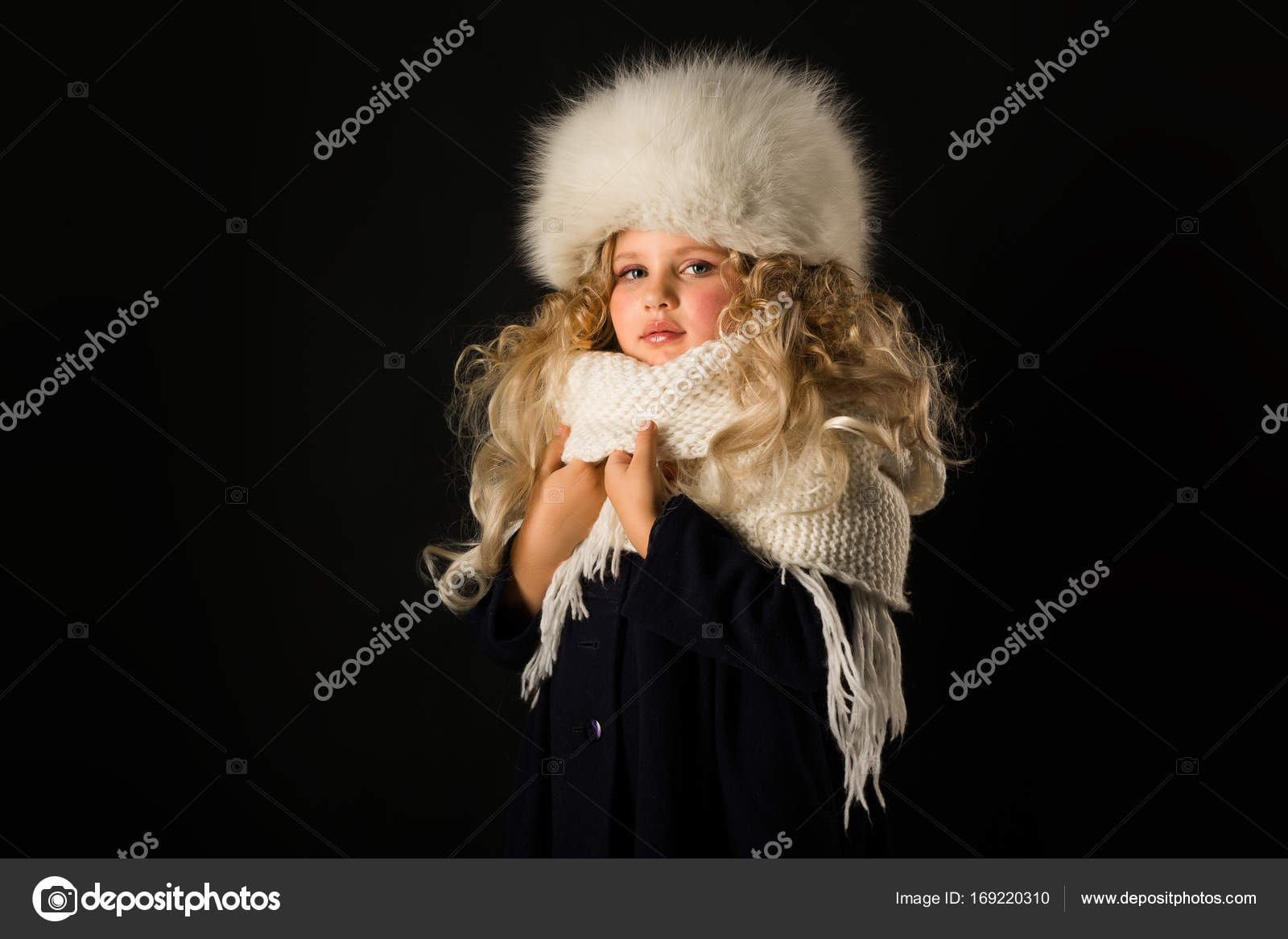 74c643edbd6b15 Isolated on black, beautiful caucasian blonde little girl in dark blue coat,  white scarf and white fur hat, serious look — Photo by fotoevent.stock