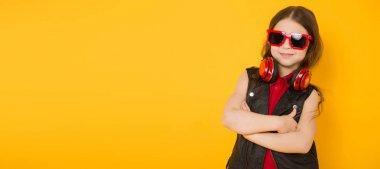 Cute little brunette girl in sunglasses and modern headphones listening to music