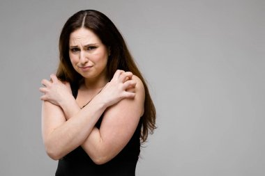 Beautiful curvy brunette woman with long luxurious hair in simple black shirt showing different expressions on grey wall in studio. Crossing hands like it is cold.