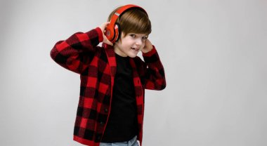 Nice preteen caucasian boy in casual outfit listening to music in red headphones and showing different expressions on white wall in studio.