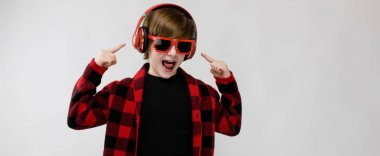 Nice preteen caucasian boy in casual outfit, red headphones and sunglasses showing different expressions on white wall in studio.