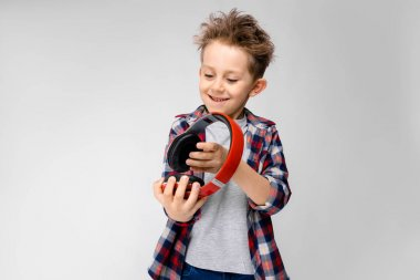 Nice caucasian preschooler boy in casual outfit posing with red headphones and showing different expressions on white wall in studio.