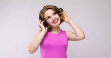 Portrait of beautiful redhead happy young woman listening music in headphones on gray background