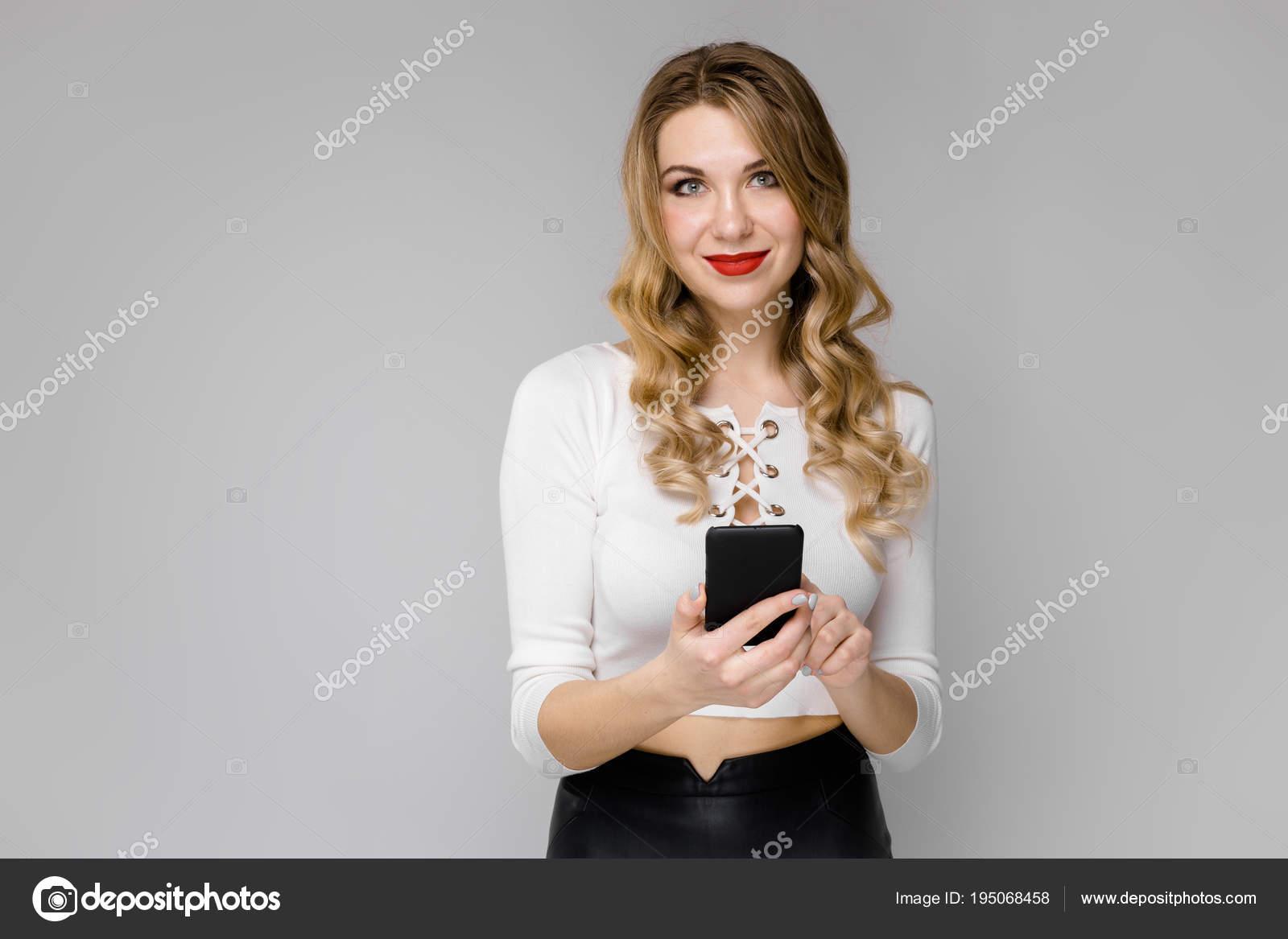 4aa1d60c22e2 Attraente giovane donna bionda di affari in vestiti in bianco e nero  sorridente che tiene telefono mobile nelle sue mani in piedi nell ufficio su  sfondo ...