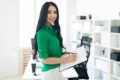 Fotografie junge Brünette Frau in grüne Bluse und weiße Hosen im Büro mit Dokumenten stehen
