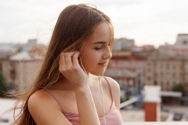 Young woman with headphones dangling on her mobile phone