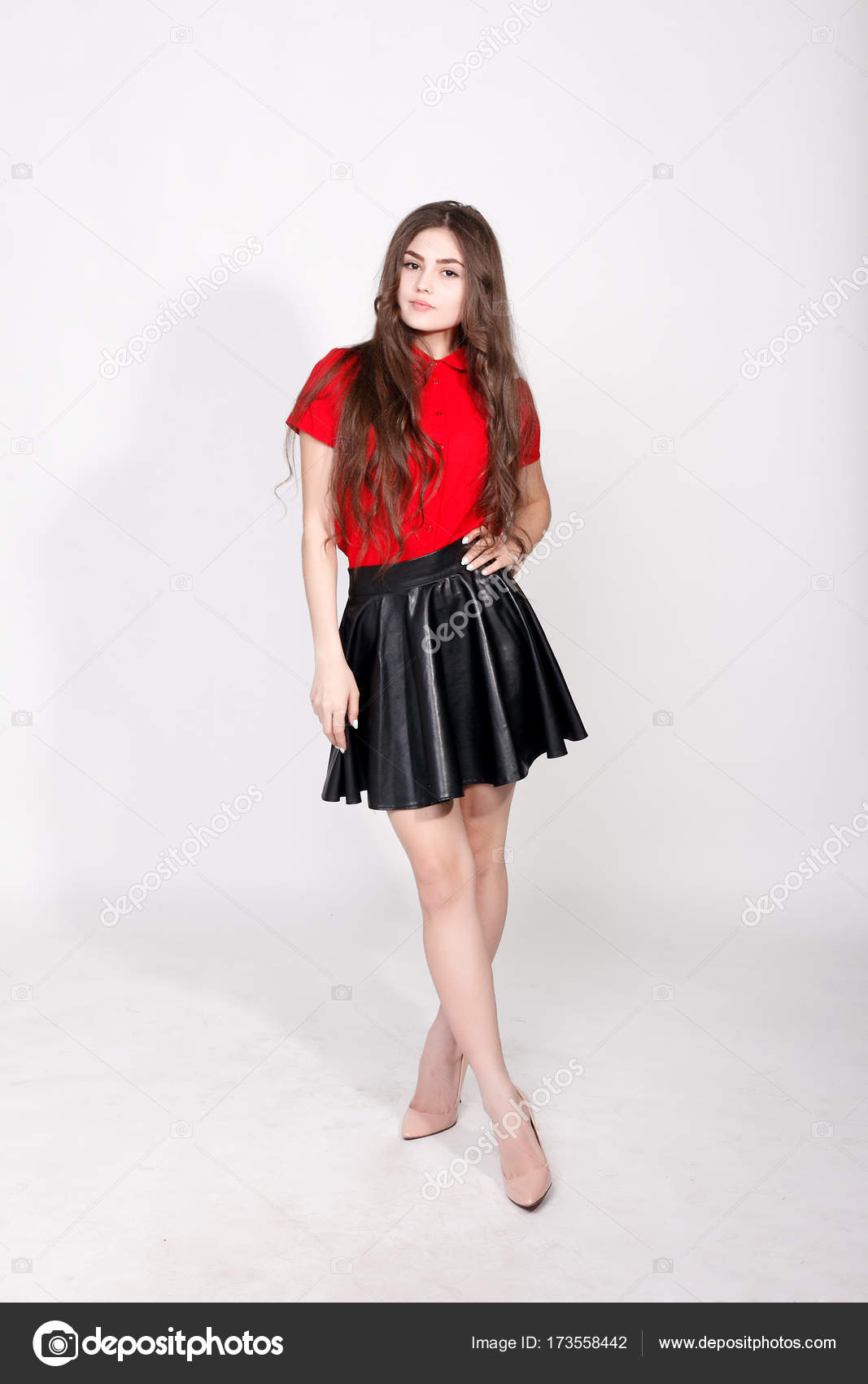 1f8f986239 Teeth,emotions, health, people and lifestyle concept - Fashionable young  brunette woman posing wearing leather skirt and red shirt, looking at  camera.