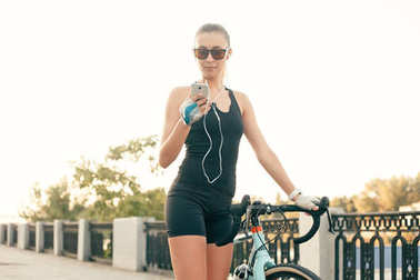 Beautiful girl with a bike, a phone and headphones