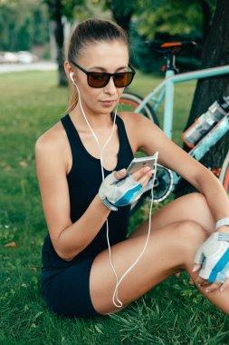Beautiful girl with a bike, a phone and headphones