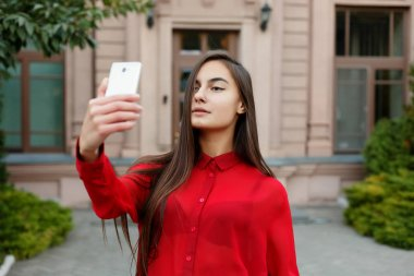 portrait of young attractive female in stylish outfit making selfie