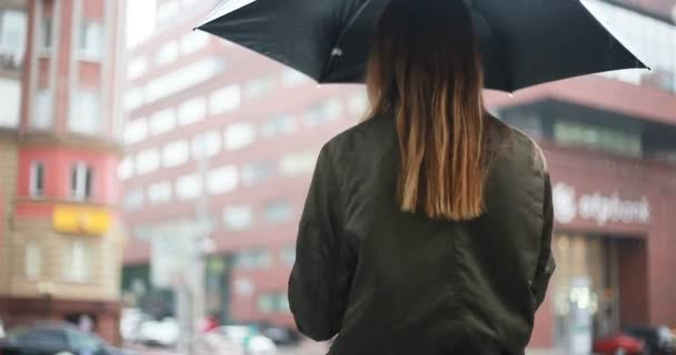 season, weather and people concept - Young brunette woman stands with umbrella in her hand on the street on rainy day