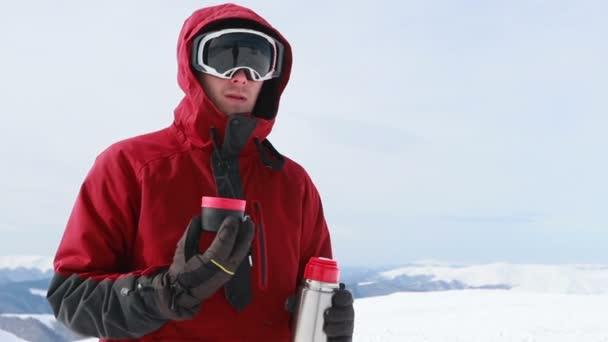 Mann junger Snowboarder außerhalb Winterskigebiet suchen Kamera fröhlich Lächeln blaue Augen Helm Aktivität Sport Lifestyle extreme männliche Person Berge Skifahren Menschen. Tee aus der Thermoskanne trinken