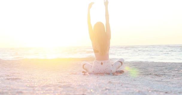Egy fiatal nő testruhában jógázik a tengerparton, csodálatos napfelkeltekor. Fitness, sport, jóga és egészséges életmód koncepció. Lassú mozgás..