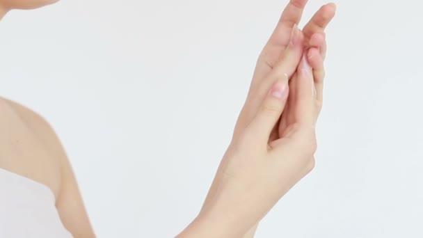 krása, lidé a zdraví koncept - Čisté dobře upravené ruce mladé ženy nanášení krému na ruce, péče o pleť na bílém pozadí. detailní záběr. Smyslná žena hydratuje pleť. 4K, zpomalený pohyb