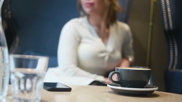 Beautiful thoughtful woman having coffee in cafe. Half face portrait of drinking coffee young woman.