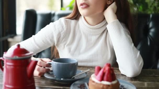 Morning tea with gadgets of beautiful woman in cafe. Close up pleasant face of attractive female drink hot beverage from cup. Smiling woman enjoying coffee or tea at cafe having positive emotion. 4k