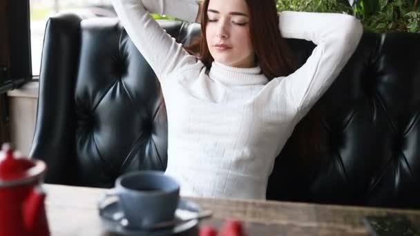 Šťastná mladá žena odpočívající a snící na pohodlném gauči. Uvolněná tisíciletá dívka se dívá stranou, usmívá se a užívá si salonek doma. Klidná dáma sní, necítí žádný stres
