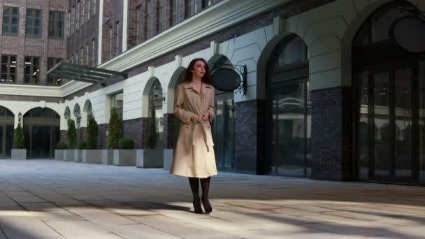 Svůdná mladá žena s dokonalým tělem v béžové pláštěnce pózující městský den na jaře. Bruneta model dívka v módní jarní oblečení pózování na městském pozadí. Model s černým sexy spodní prádlo