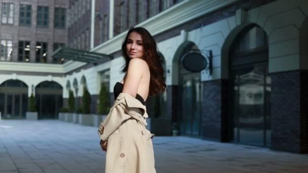 Verführerische junge Frau mit perfektem Körper in beigem Regenmantel, die an diesem Frühlingstag auf der Straße posiert. Brünettes Model Mädchen im modischen Frühlings-Outfit posiert vor urbanem Hintergrund. Modell mit schwarzen sexy Dessous