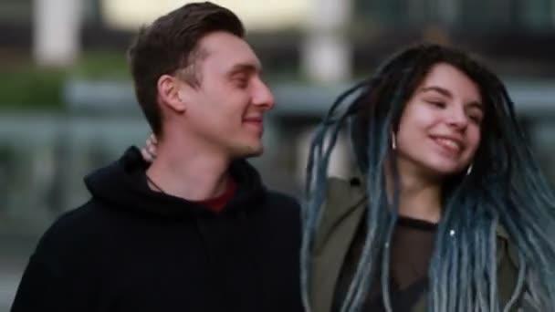 Junges glückliches Liebespaar, das draußen auf der Straße spazieren geht und Spaß hat. Paar hält Händchen. Ein verliebtes Paar, das Spaß und Freude hat und sich umarmt. Frau mit Dreadlocks. Kuss