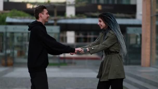 Mladý šťastný milující pár procházky venku na ulici se baví. Pár Chyťte se za ruce. Pár zamilovaný zábavy a radosti objímající se spolu. žena s dredy. pusa