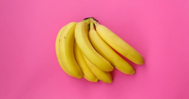A banánok táncolnak. Ne mozgasd az animációs gyümölcsöt. Élelmiszer, egészséges táplálkozás és vegetáriánus fogalom. Absztrakt színes animáció - banánrózsaszín háttér. 4K