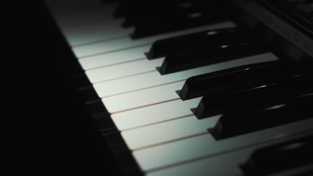 Pianist spielt sanfte klassische Musik auf einem schönen Flügel mit einer Hand Nahaufnahme in Zeitlupe. Klaviertasten schließen sich in dunklen Farben. Studenten bilden aus. Hände eines Männchens in schwachem Licht. 4K