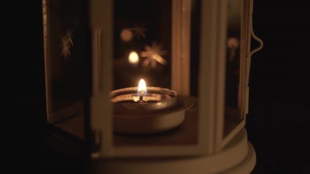 Lucerna se svíčkou zblízka. Bílá lucerna s hvězdami a hořící svíčkou uvnitř na stole venku v noci.