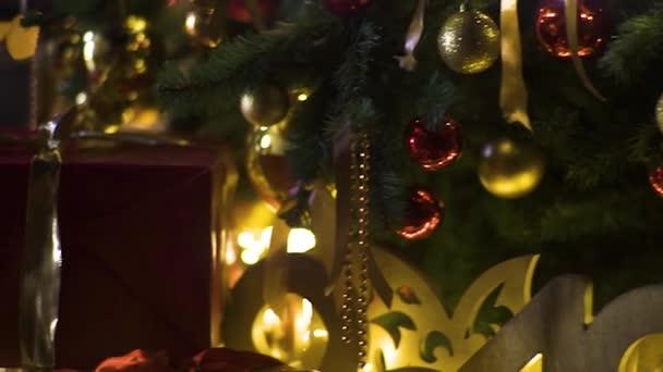 Zavři v noci světla na vánočním stromku. Novozélandský strom s dekoracemi a osvětlením. Pozadí dekorace Xmas. Mnoho velkých zlatých koulí na jedlém stromě nový rok a Vánoce