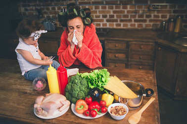 Stressed mum at home. Young mother with little child in the home kitchen. Woman doing many tasks while looks after her baby. The woman is sick and she has a runny nose.