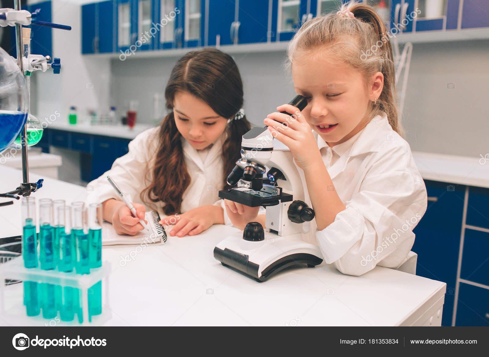 Zwei kleine kinder im laborkittel lernen im schülerlabor chemie