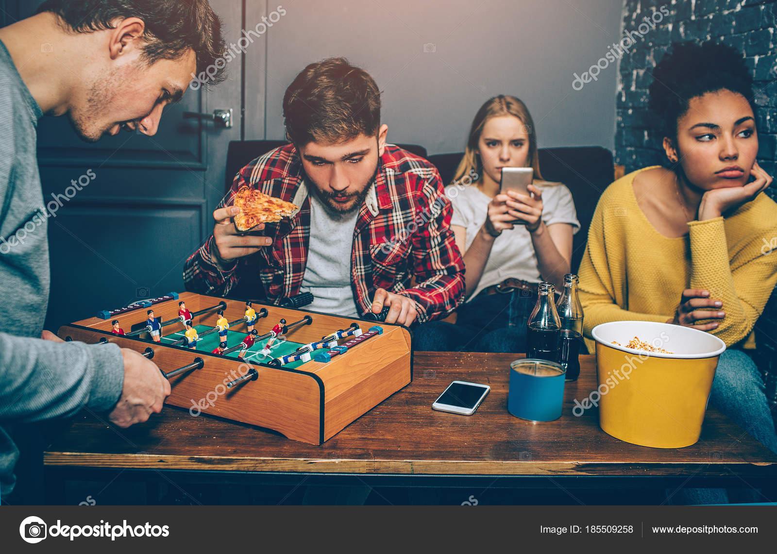 Dos niños están jugando tablero de juego de fútbol. Están muy concentrados  en él mientras que las niñas están viendo en el teléfono y sensación  aburridas. 65f3e64e9ca53