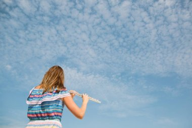 young beautiful woman playing the flute against blue sky