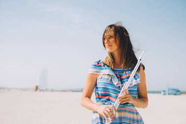 young beautiful woman holding the flute at beach