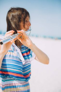 young beautiful woman playing the flute at beach