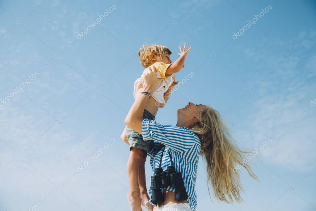 young mother holding happy little son against blue sky