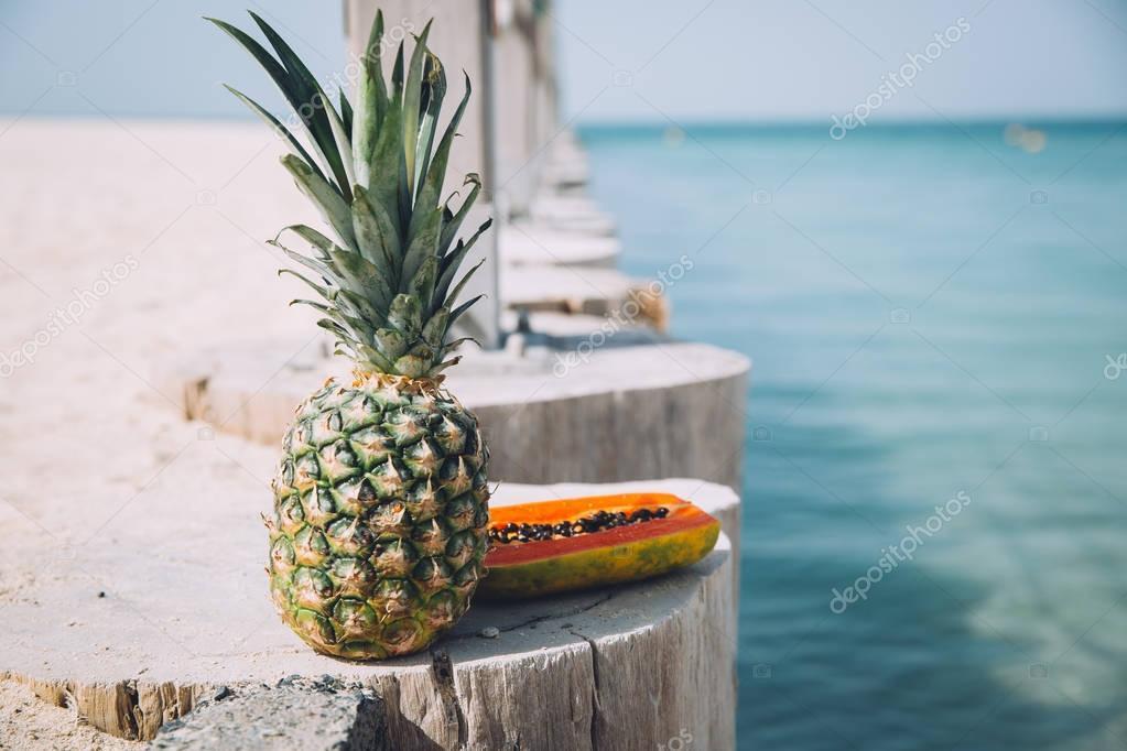 summer picnic at pier, tropical fruits near sea, papaya and pineapple