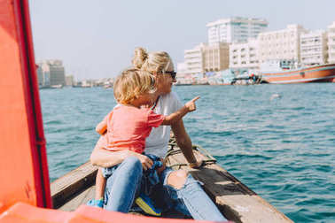 young beautiful woman with her little son sitting at boat and contemplating the seascape