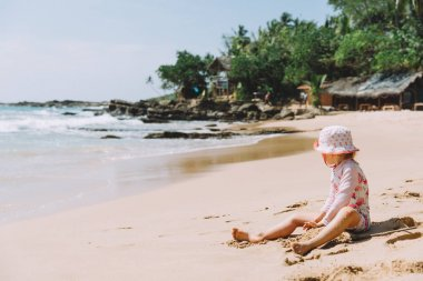 adorable little girl playing with sand at tropical beach