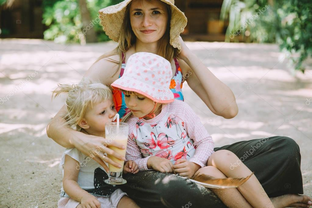 young mother with cute little daughters relaxing at sandy tropical beach
