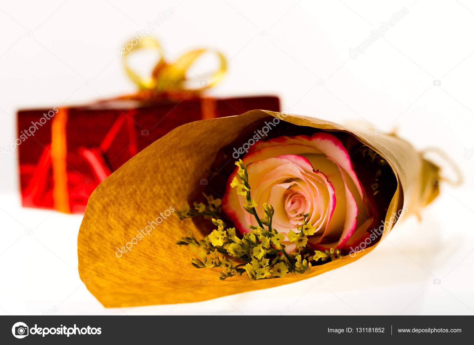 Bouquet Of Flowers In Parchment Paper And Wrapped Gift On A Whit