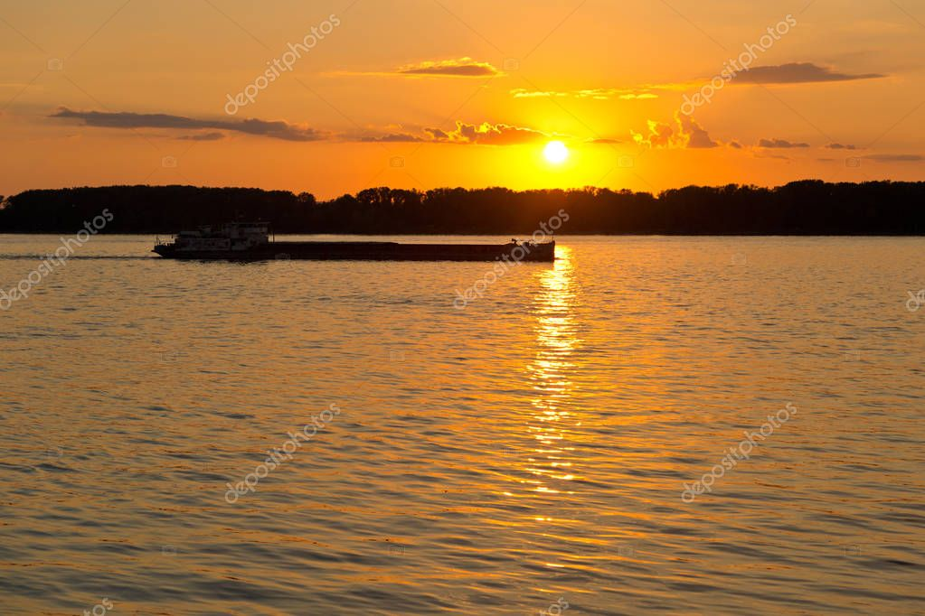 barge passes through the channel of the river Volga, breaking the light beam reflected on the water of the setting sun.