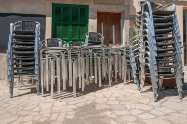 Metal chairs stacked next to outdoor tables. Restaurant businesses closed by Coronavirus