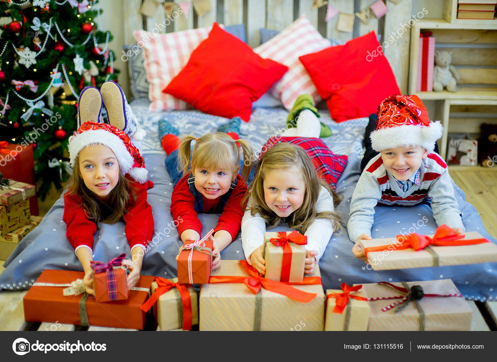 group of kids in red hat with christmas gifts stock photo