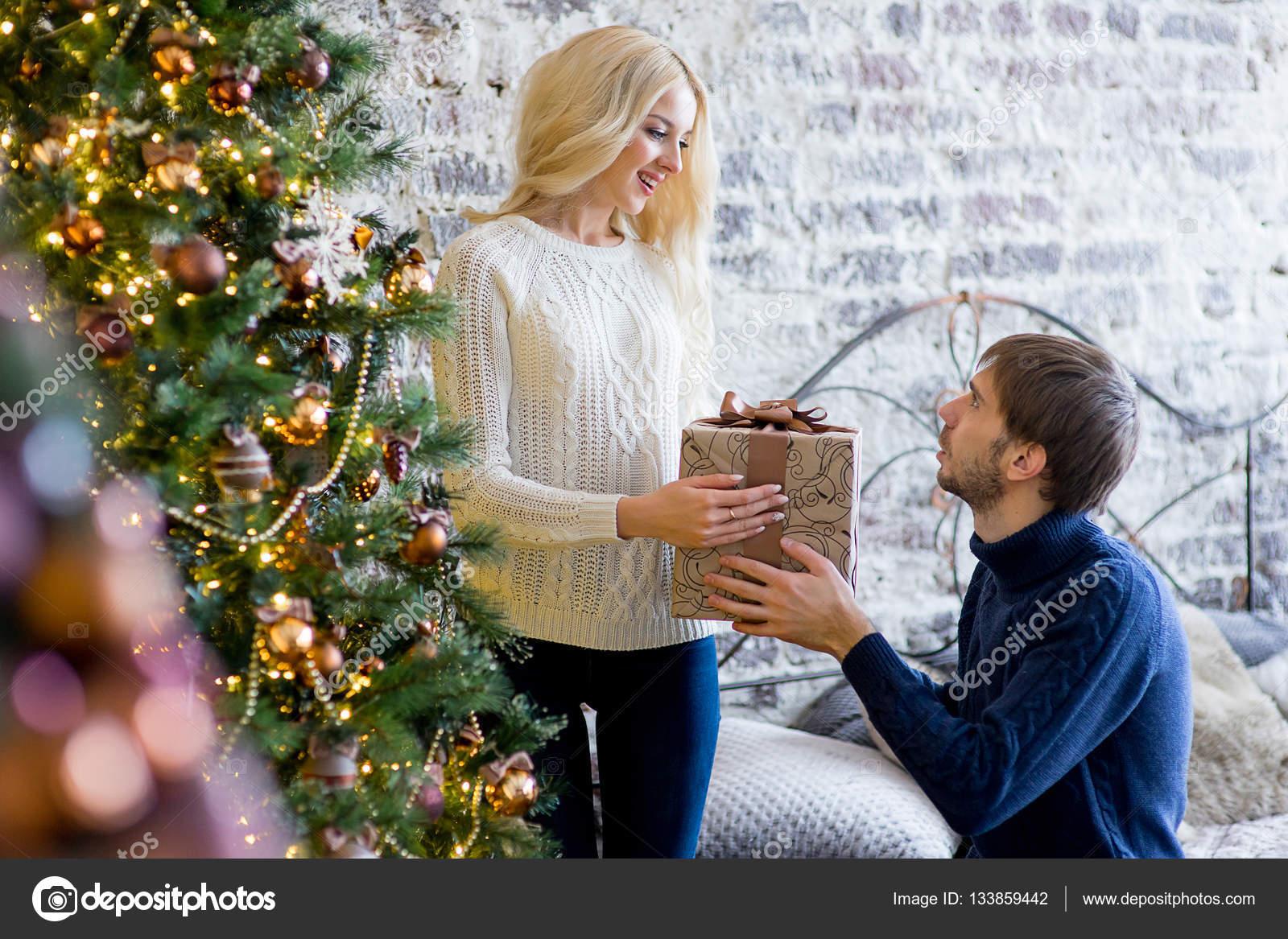 Mann ein Geschenk mit dem Mädchen machen, während sie Weihnachten ...